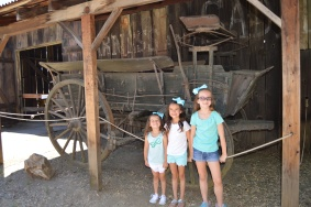 Lila, Caitlyn and Emily in front of an old wagon